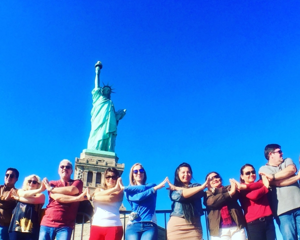 People holding hands in front of statue of liberty